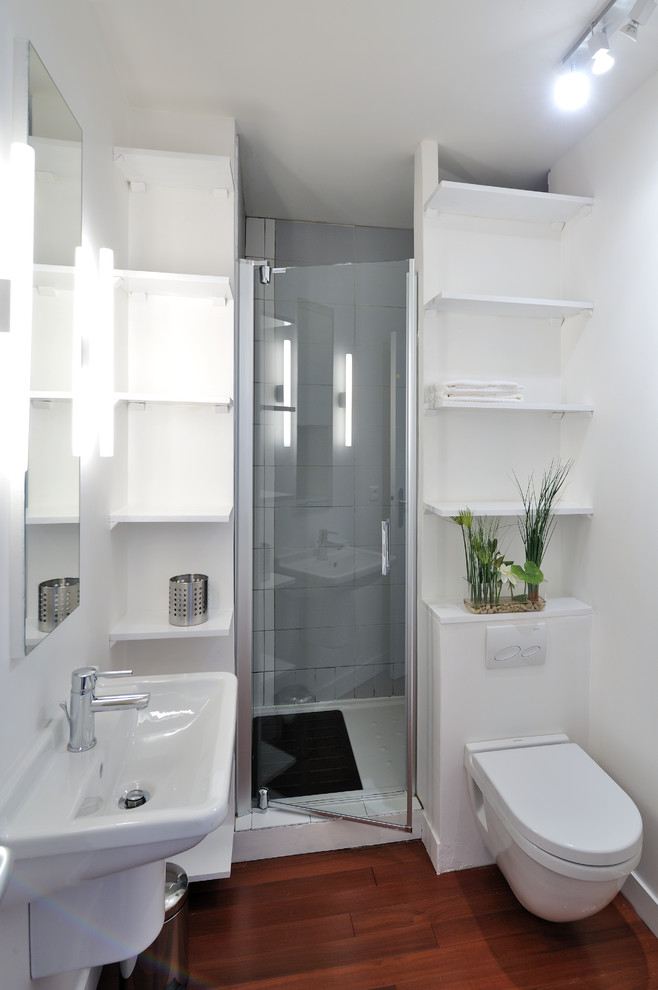 white small bathroom with wooden flooring, white toilet, white shelves, white sink, white tiles on shower area