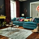 Eclectic living room with medium toned wooden floors rug blue sofa and multicolored pillow throws distinctive wooden coffee table artificial plant black wall