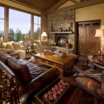 Huge tuscan formal and open concept medium tone wood floor living room with a standard fireplace, a stone fireplace, yellow walls and a concealed tv