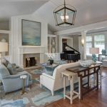 Large transitional formal and open concept medium tone wood floor living room with a standard fireplace, a stone fireplace, white walls and no tv