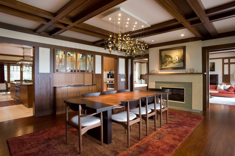 Mid century modern dining room with brown rug medium toned wooden floors a chandelier lamp white wall wooden floors wooden cabinetry wall artwork