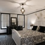 Trendy Dark Wood Floor Bedroom With White Walls White Bedding Black And White Rug Pendant Lamp Table Lamp Black Table