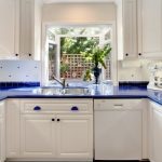 Bay Window Double Sink White Cabinet White Appliances Blue Countertop Blue Holder Tiled Backsplash