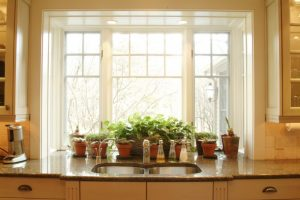 bay window kitchen bay window white trim sink plants pots granite countertop tiled backsplash white cabinet over sink lights