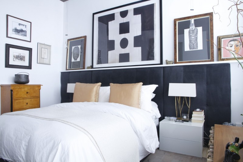 eclectic bedroom with white walls black and white arts furnished wooden cabinets black headboard golden pillows table lamps white tables
