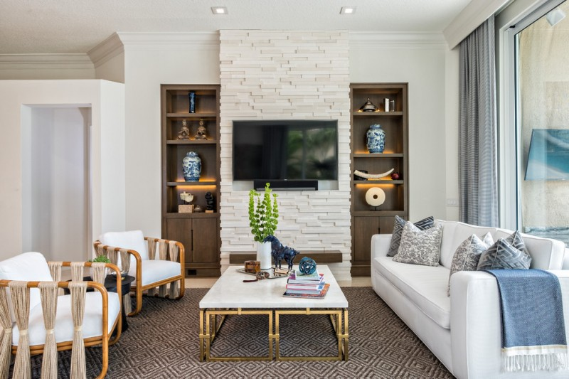 large contemporary open concept limestone floor living room with white walls, a stone fireplace and a wall mounted tv wooden accent chairs