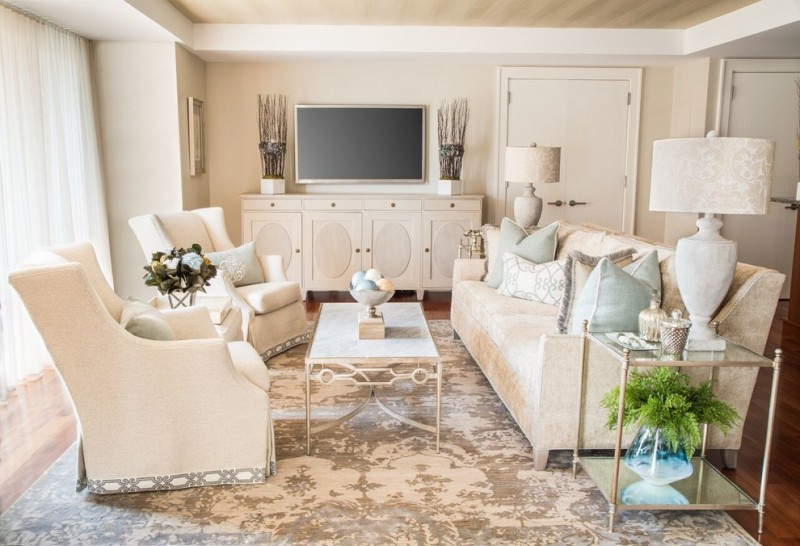 large timeless open concept medium tone wood floor living room with beige walls, cabinets, sofas and coffee table and a wall mounted TV