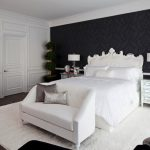 large transitional master dark wood floor bedroom with black walls white carpet chandelier lamp white framed mirror table lamps white cabinet white sofa and pillow throws