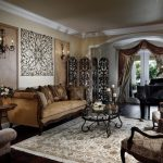 ornate living room with a music area and beige walls white table lamp brown sofas brown accent rug glass coffee table medium toned wooden floors