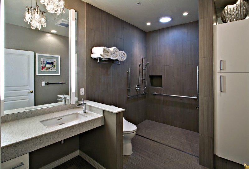 brown bathroom brown tile floor brown wall tile sink hanging pendant light open shower open vanity oversized bathroom mirror thick slab counter countertop towel shelf walk in shower