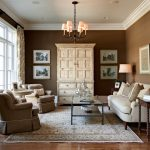 Brown Living Room Area Rug Arm Chairs Artwork Chandelier Coffee Table Crown Molding Curtain Panels Dark Stained Wood Sofa Wood Floor