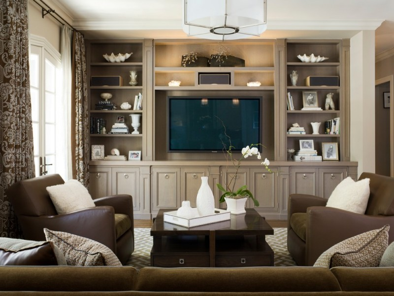 built in tv cabinet beige wall brown leather armchairs brown patterned curtain brown sofa built in shelves white chandelier brown coffee table white accents