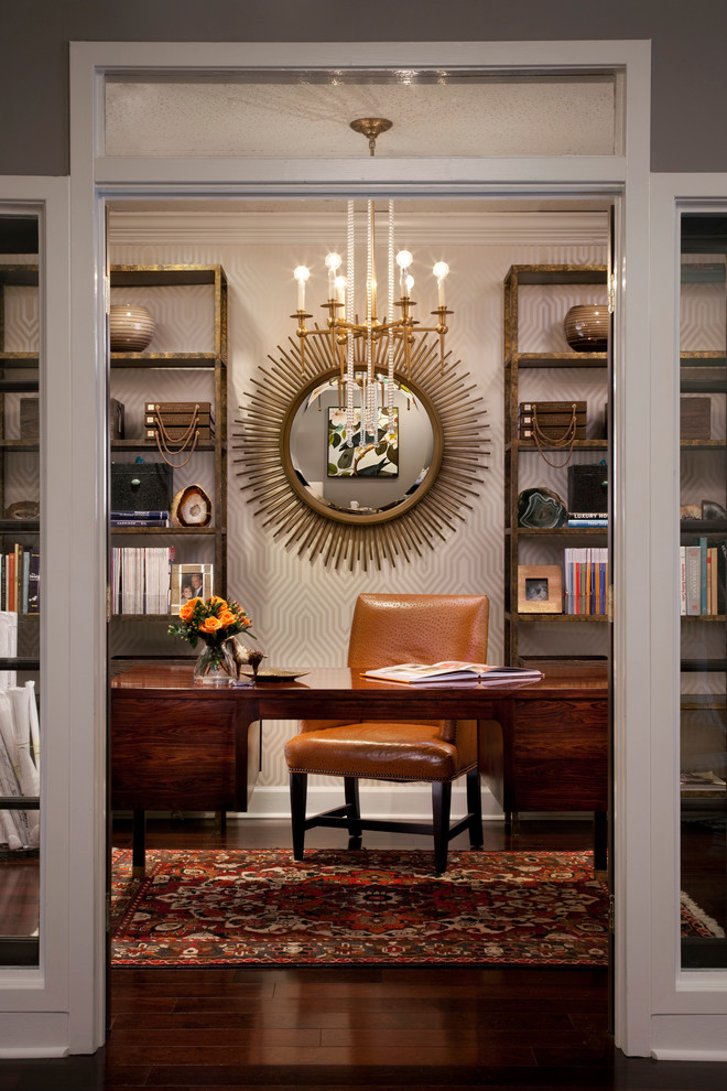 office wallpaper bold bookshelf brass and glass chandelier dark wood desk dark wood floor glass wall bookcase gold chandelier gold sunburst mirror hickory chair khotan rug leather chair metal bookcas
