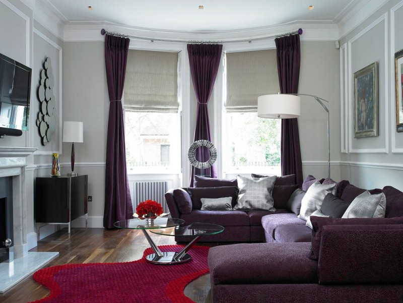 purple sofa multi circle mirror purple curtains unique red rug light grey roman blinds windows wooden floor floor lamp glass table