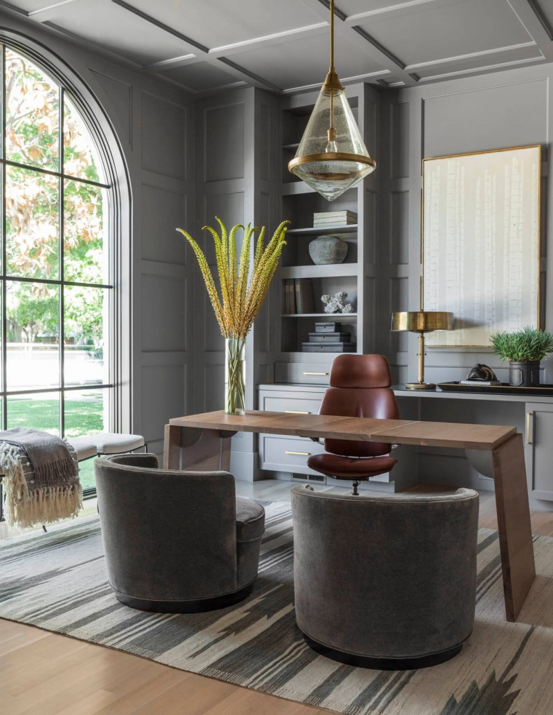 area rug arched window grey desk chair brown office chair wooden table freestanding table built in bookcase open shelves paneled ceiling pendant light