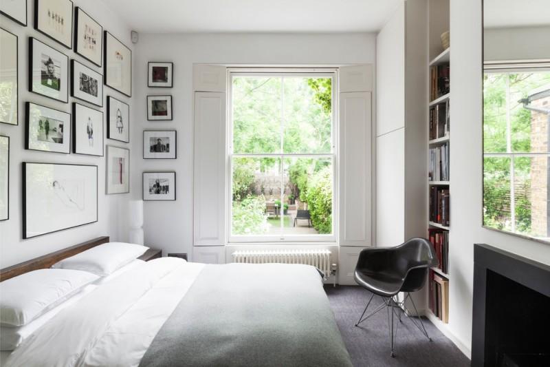 art deco bedroom vitra eames dining armchair built in bookshelves white room black and white framed wall gallery dark wood floor white bed grey blanket windows