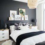 Black Bedroom Beige Pendant Light Black Accent Wall Framed Art Gray Rug Black Throw White Nightstands Black Table Lamps