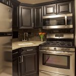 Corner Sink Cabinet Dark Wood Cabinets Floral Arrangement Granite Countertops Kitchen Hardware Stainless Steel Appliances Subway Tiles Dark Tile Backsplash