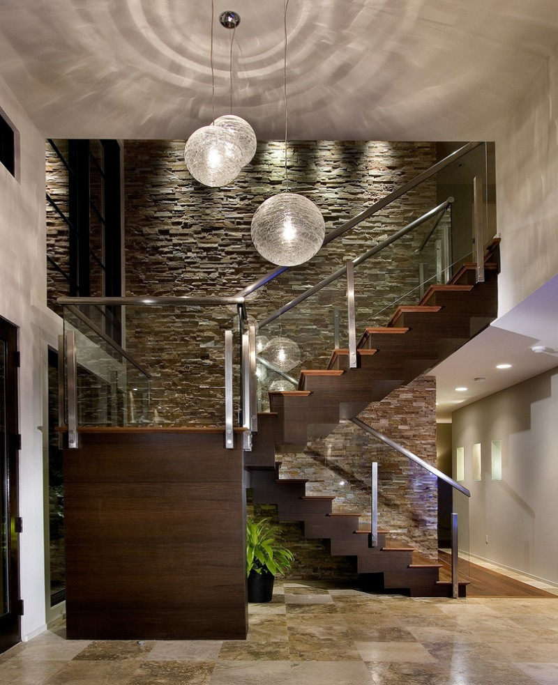 glass stair railing stones wall wood stairs three chandelier ceramic floor indoor plants recessed lighting glass doors and windows