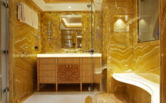 gold bathroom ceiling treatment high gloss marbled mirror storage vanity towel bar shower glass door shower bench sink and cabinet white countertop