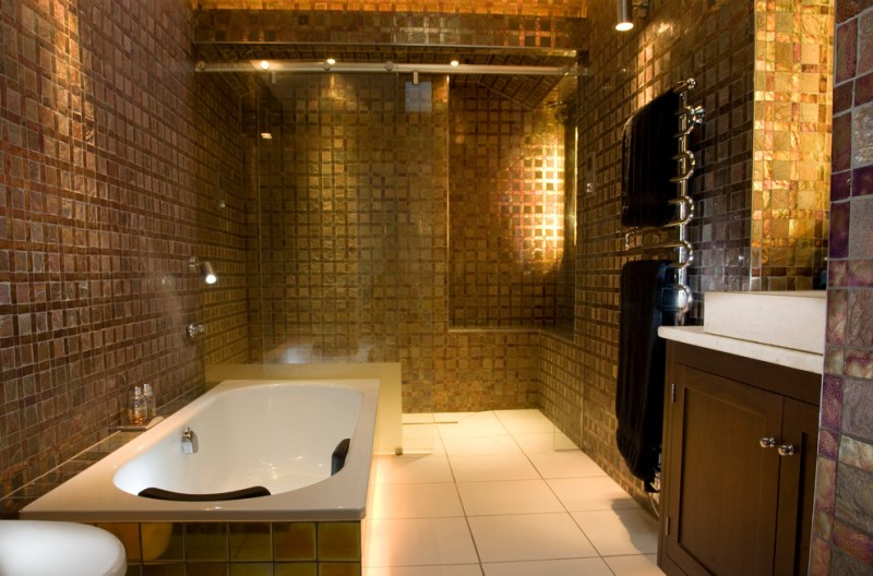 gold bathroom downlights fired earth gold bathroom tiles towel rack white sink wooden vanity tub with gold tiles shower glass door