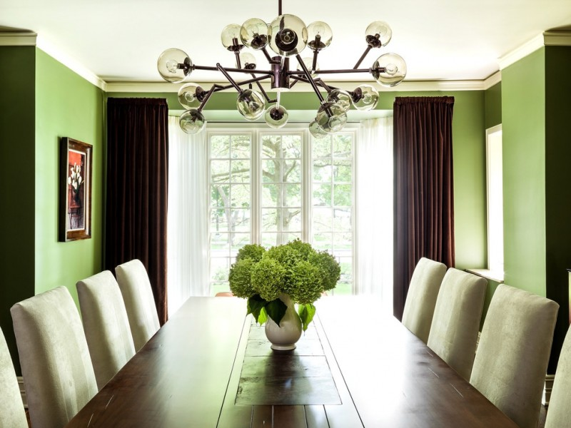 green dining room dining table and chairs brown curtains green walls chandelier artwork flowers white windows