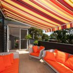 Modern Awning Bright Colours Covered Deck Glass Door Orange Outdoor Cushions Orange Throw Pillows Outdoor Furniture