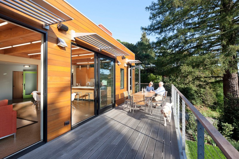 modern awning cable railing cedar siding wood deck outdoor dining sliding glass doors sun shades wall sconce wood cladding