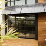 Modern Awning Solar Paneling Glass Walls Glass Windows Sliding Glass Doors With Black Frame Wood Wall Wall Sconce Railing