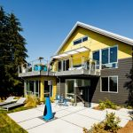 Modern Awning Yellow And Brown House Outdoor Furniture Blue Chairs Black Glass Windows And Doors Patio Small Garden