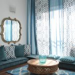 Moroccan Coffee Table Blue Area Rug Curtains Floor Cushions Blue Glass Big Antique Mirror White Wall Wood Flooring Pillows