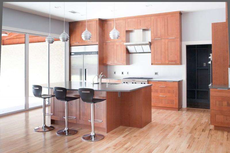 pendant lights medium tone wooden floor medium tone wooden cabinetry island undermount sink zinc countertop glass door sliding door