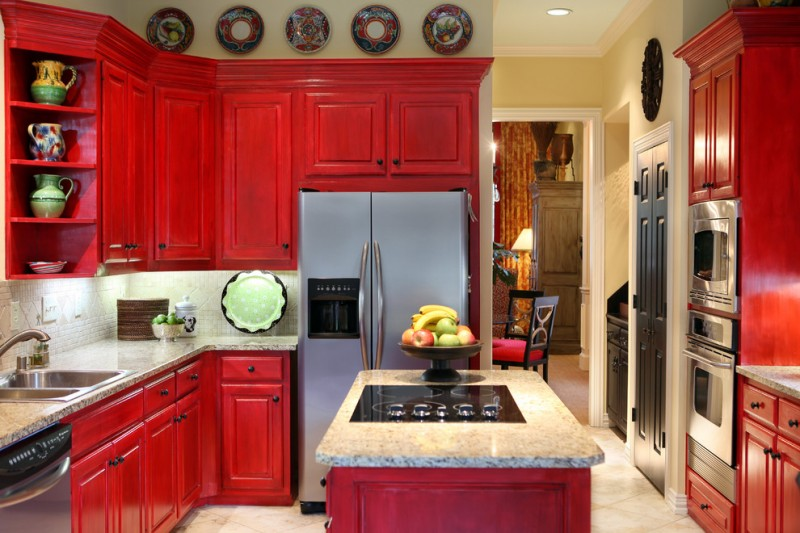 red cabinets beige stone floor beige tile backsplash cooktop double kitchen sink fruit bowl granite countertop kitchen island open shelves wall decor