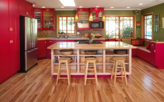 red cabinets bookshelves colorful kitchen cookbook storage glass cabinets green wall kitchen island kitchen island storage marble countertop patterned tile backsplash barstools