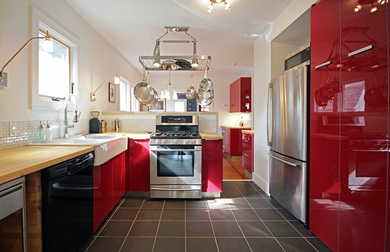 red cabinets sconces slanted roof stainless steel appliances rectangle floor tile hanging kitchen pans, window wood coutertops white wall