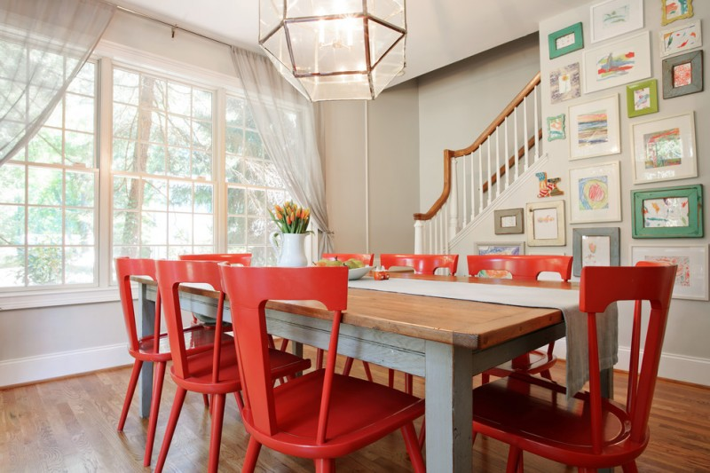 red chairs large wooden table rustic chandelier stairs wood railing framed paintings wood floor sliding glass french doors curtains