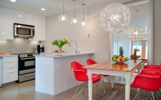 red chairs white chandelier big mirror wooden table fruits brown floor white kitchen cabinet built in oven sink kitchen island