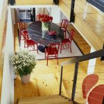 Red Chairs Wood Stairs And Railings Dark Marble Saarinen Oval Dining Table Wood Floor Flower Arrangement Indoor Plants Area Rug