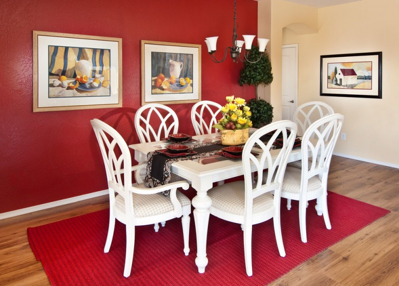 red dining room red wall red rug white dining table and chairs artwork wood flooring chandelier indoor plants flowers arrangement