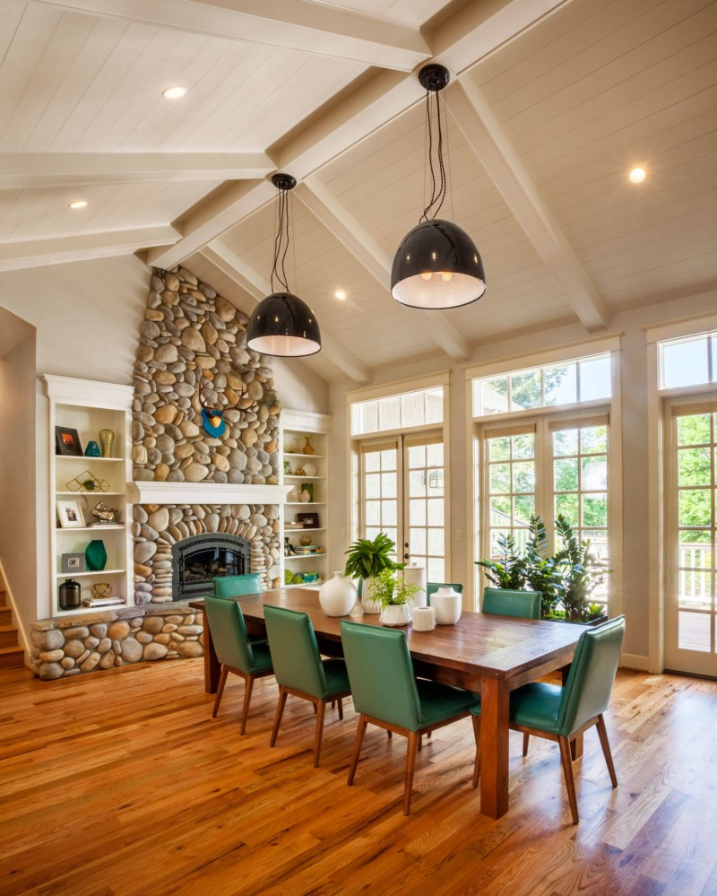 sloped ceiling pendant light medium tone wood floor wood table green chair glass door stone fireplace built in shelves