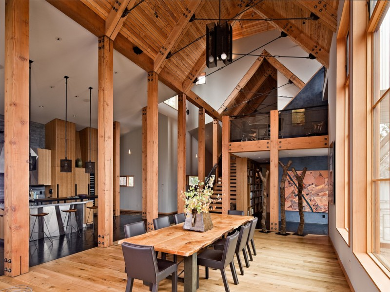 sloped ceiling wood dining table brown chairs light brown flooring stairs unique light fixture glass windows kitchen barstools