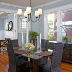 Square Pedestal Table Baseboards Chandelier Crown Molding Black Chairs French Doors Orchid Potted Plants Wood Floor