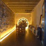 Textured Wall Glass Door Wine Cellar Man Cave Lighting Exposed Beams Tiled Floor Wooden Sitting Space Wine Rack
