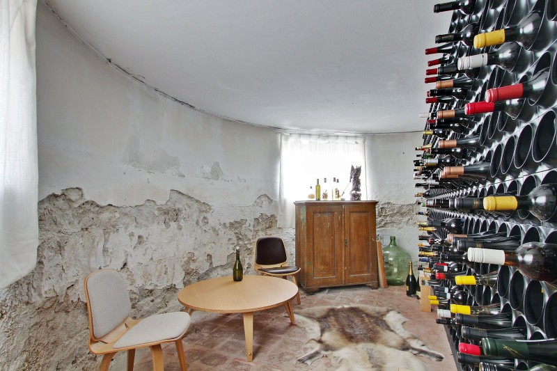 wine cellar wine storage leather rug raw wall wooden sideboard wooden coffee table low chair stone floor