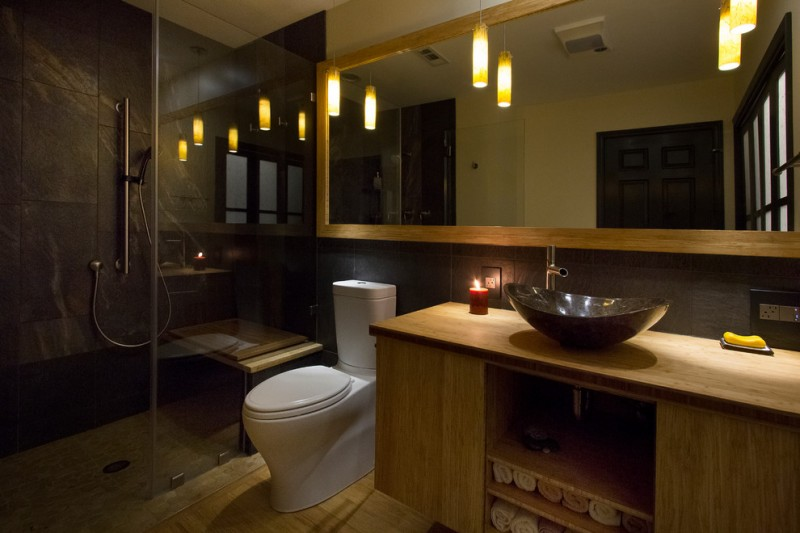bamboo bathroom wide mirror pendant lights dark stone wall bench shower head wood vanity black sink bowl candle towels