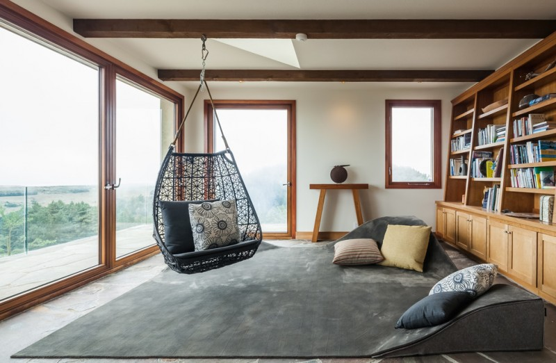 hanging papasan chairs black hanging chair carpet and floor cushions pillows wooden book shelves window big glass doors