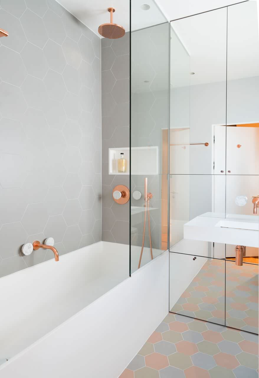 hexagonal tiles white bathtub ceiling shower mirrored panelled cabinet white sink glass siding