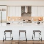 Modern Chic Kitchen Barstools White Kitchen Cabinets White Kitchen Island Grey Backsplash Recessed Lighting Undermount Sink Hood Wood Floor