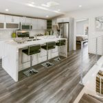 Modern Chic Kitchen Green Barstools Granite Kitchen Island White Kitchen Cabinets Recessed Lighting Wood Flooring Undermount Sink Railing