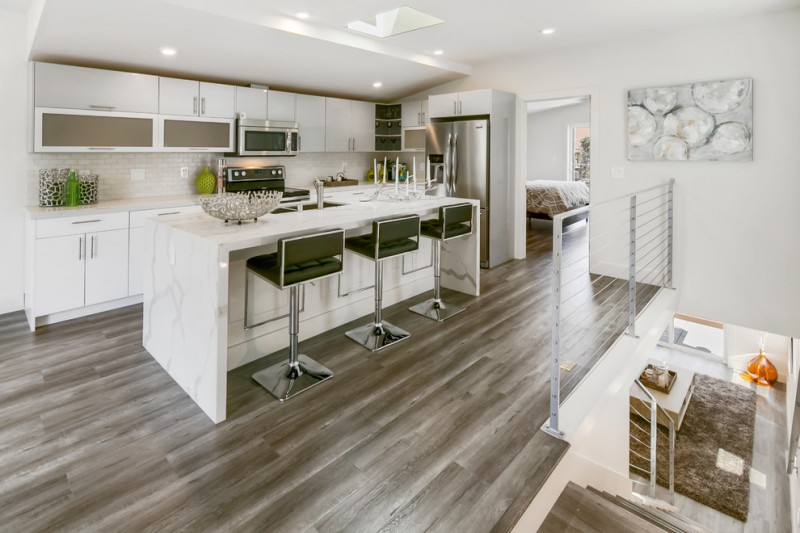 modern chic kitchen green barstools granite kitchen island white kitchen cabinets recessed lighting wood flooring undermount sink railing